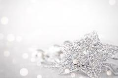 星和发光的银色装饰品在明亮的抽象背景bokeh 免版税库存图片
