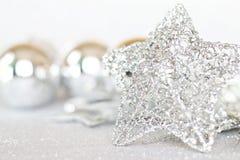 星和发光的银色装饰品在明亮的抽象背景bokeh 库存照片