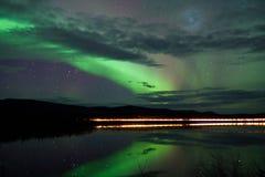 星形和在黑暗的路的北极光在湖 免版税库存图片