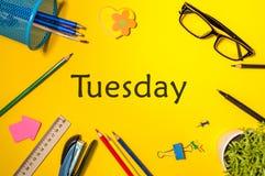 星期二 办公用品或学生成套装备在黄色桌上 企业创造性的概念,顶视图 免版税库存照片