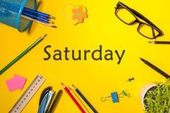 星期六-在黄色工作场所的词顶视图有办公室或学校用品的 时间安排和日程表概念 免版税库存图片