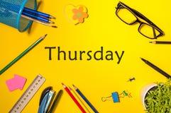 星期四 办公用品或学生成套装备在黄色桌上 企业创造性的概念,顶视图 免版税库存图片