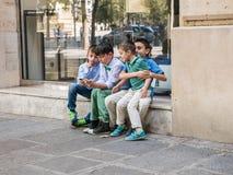 星期天衣裳的小男孩学习在巴黎街道上的一个智能手机 免版税库存图片