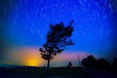 星落后,火飞行和在农场的北极光 库存照片