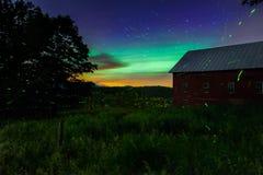 星落后,火飞行和在农场的北极光 免版税库存照片