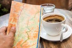 映射在手中,在木桌上的咖啡杯 库存照片