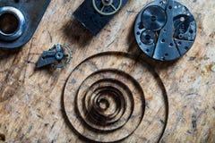 春天、摆轮和钟表机构在桌上 库存图片