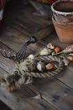 春天与园艺工具和陶瓷罐的装饰灯泡在木桌上 免版税库存图片