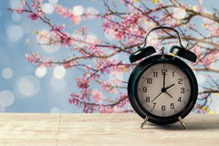 春天与闹钟的变动概念在自然树开花的木桌上 库存照片