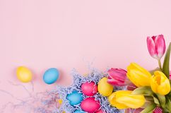 春天复活节欢乐背景-自创被绘的多彩多姿的鸡蛋,在淡色浅粉红色的背景的郁金香花束 库存图片