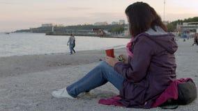 春天外套的花姑娘坐与杯子的海滩热的饮料并且使用她的电话的4K 股票视频