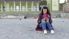 春天外套的花姑娘坐与杯子的海滩热的饮料并且使用她的电话的4K 影视素材