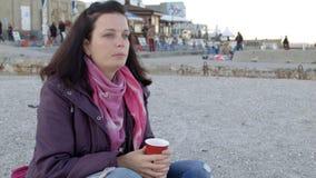春天外套的花姑娘坐与杯子的海滩热的饮料的4K 股票视频