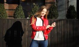 春天夹克的女孩在咖啡馆附近站立 免版税库存图片
