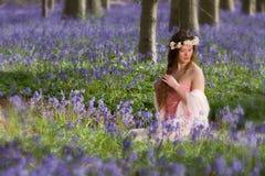 春天女孩在会开蓝色钟形花的草森林里 库存照片