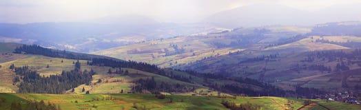 春天山全景 云彩和太阳在小山 库存照片