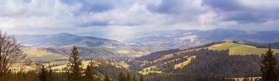春天山全景 云彩和太阳在小山 库存图片