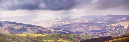 春天山全景 云彩和太阳在小山 免版税库存图片