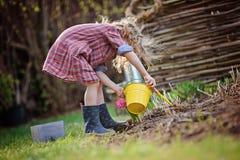 春天庭院戏剧和种植风信花的漂亮的孩子女孩开花 免版税库存图片