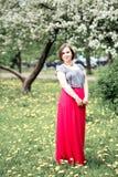 春天开花树的年轻美丽的妇女 免版税库存图片