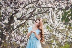 春天接触 蓝色礼服的愉快的美丽的年轻微笑的妇女享受鲜花和太阳光在开花公园在 库存照片