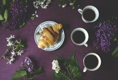 春天早餐:咖啡、新月形面包和花 库存图片