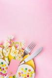 春天桌与板材,利器,水仙的餐位餐具开花束、蛋糕和空白的标记在粉红彩笔背景,顶视图 图库摄影