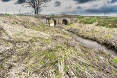 水春天流程在一条小河的床上穿过大排水设备管子在大块桥梁下 库存图片