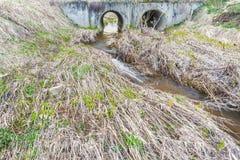 水春天流程在一条小河的床上穿过大排水设备管子在大块桥梁下 免版税库存照片