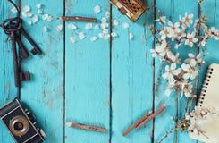 春天白色樱花树,空白的笔记本,在蓝色木桌上的老照相机的顶视图图象 免版税库存照片