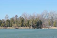 春天的冻湖在纪念公园Constantin Stere在Bucov,在普洛耶什蒂附近,罗马尼亚 免版税库存照片