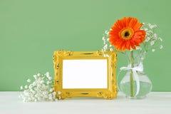 春天美丽的花束的图象在木桌上的空白的葡萄酒照片框架旁边开花 对蒙太奇的摄影嘲笑 库存照片