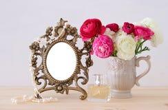春天花、香水瓶和珍珠在空白的葡萄酒照片框架旁边 库存照片