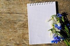 春天花和笔记薄花束在木背景 免版税库存图片