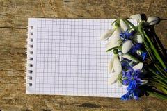 春天花和笔记薄花束在木背景 免版税库存照片