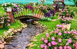 春天花在有池塘的庭院里 免版税库存照片