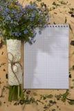 春天花束忘记我在笔记本的颜色在木 免版税库存图片