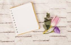 春天花:在笔记本附近的桃红色郁金香和丁香南北美洲香草 免版税库存照片
