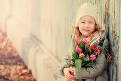 春天葡萄酒为妇女的天定调子愉快的儿童女孩画象有郁金香花束的 免版税库存照片