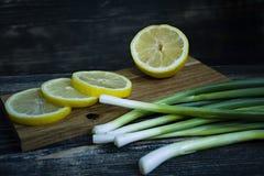 春天葱和切柠檬在黑暗的木背景 免版税库存照片
