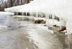 春天解冻创造在雪银行的冰柱沿小河。 库存照片