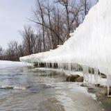 春天解冻创造在雪银行的冰柱沿小河。 免版税库存照片