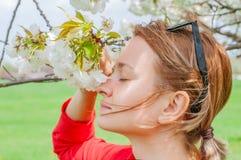 春天过敏 享用自然开花的树的美女 库存图片