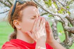 春天过敏 妇女在开花的树中打喷嚏在公园 图库摄影