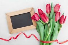 春天郁金香开花与丝带,并且与空的空间的木制框架在灰色石台式视图的文本的在舱内甲板放置样式 免版税库存图片