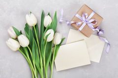 春天郁金香开花,礼物盒,并且在灰色石桌上的纸牌在舱内甲板从上面放置样式 问候为妇女或母亲节 库存图片