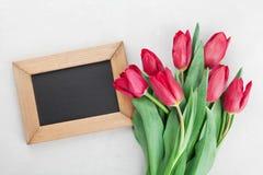 春天郁金香花和木制框架与空的空间文本的在灰色石台式视图在舱内甲板放置样式 图库摄影
