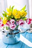 春天郁金香花束黄色和桃红色在窗口的新的平底深锅 对妇女的一件礼物 舒适房子 卡片 免版税库存照片