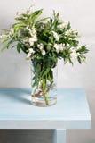 春天雪花Leucojum在玻璃花瓶的vernum花束在蓝色木桌和灰色背景上 免版税库存照片