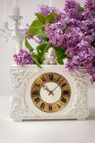 春天静物画丁香和一个时钟花束在白色背景 免版税图库摄影